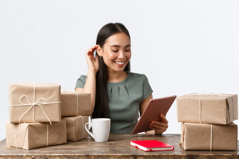 Small business owners, startup and e-commerce concept. Successful asian businesswoman with online shop, answering clients with digital tablet while drinking coffee and packign orders for shipping.