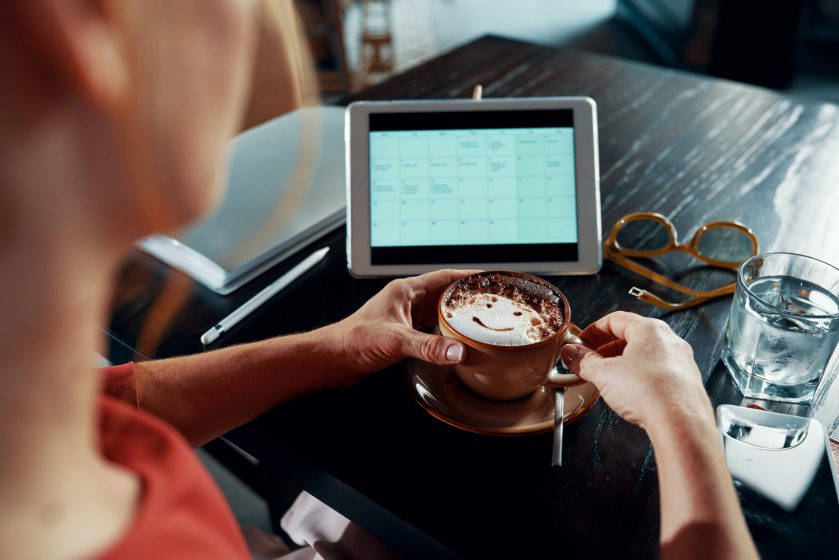 Woman enjoying big cup of cappuccino and checking calendar on tablet computer